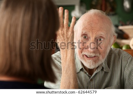 Senior couple at home in kitchen focusing on angry man - stock photo