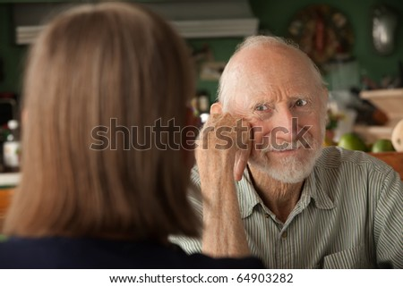 Senior couple at home in kitchen focusing on angry man