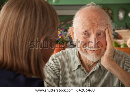 Senior couple at home in kitchen focusing on man - stock photo