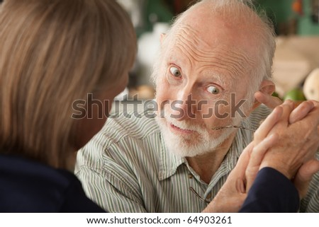 Senior couple at home in kitchen holding hands focusing on man - stock photo