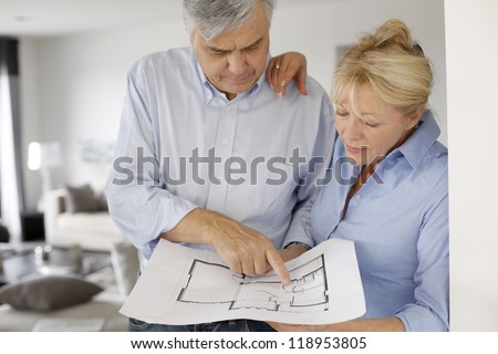 Senior couple at home looking at blueprint - stock photo
