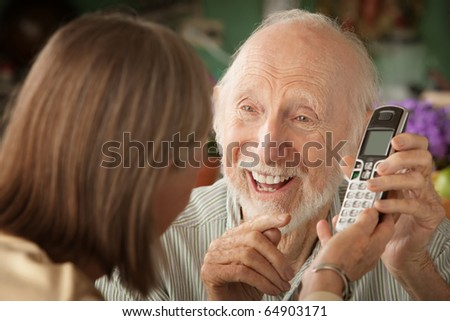 Senior couple at home with a telephone - stock photo