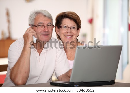Senior couple at home with laptop computer - stock photo
