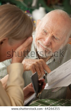 Senior couple at home with many bills - stock photo