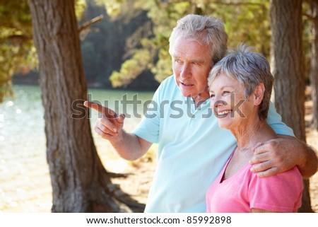 Senior couple at lake together - stock photo