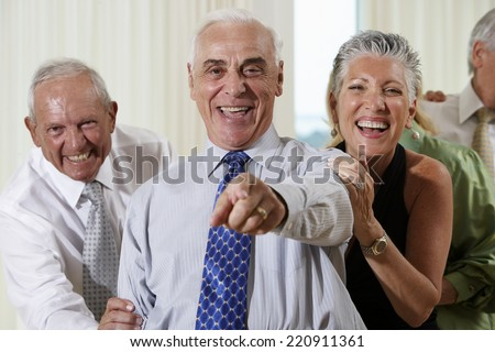 Senior couple at party pointing in surprise - stock photo