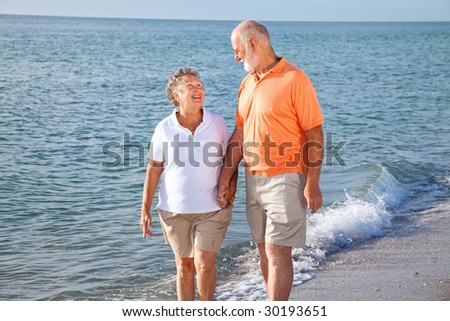 Senior couple at the beach, looking into each others eyes. - stock photo