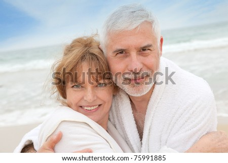 Senior couple at the beach with spa bathrobe
