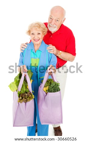 Senior couple bringing home organic produce in reusable cloth grocery bags.  Isolated on white.