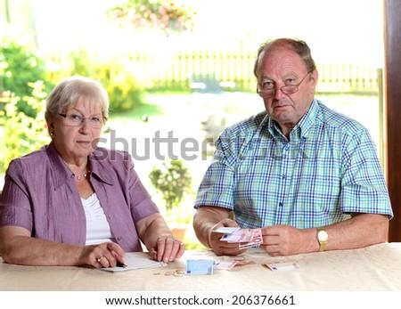 senior couple calculating her budget - stock photo