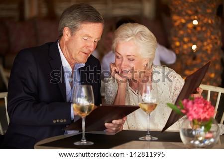 Senior Couple Choosing From Menu In Restaurant - stock photo