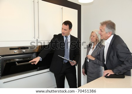 Senior couple choosing new kitchen - stock photo