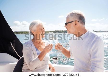 senior couple clinking glasses on boat or yacht - stock photo