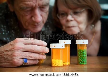 Senior couple closely examining instructions on prescription medications - stock photo