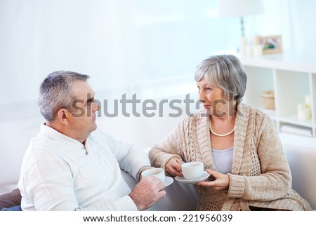 Senior couple communicating at cup of tea - stock photo
