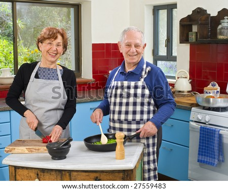 senior couple cooking at their kitchen at home - stock photo