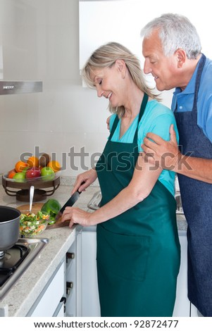 Senior couple cooking food in kitchen at home - stock photo