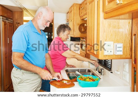 Senior couple cooking in the kitchen of their motor home. - stock photo