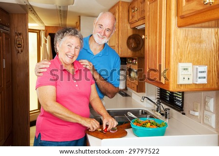 Senior couple cooking together in the kitchen of their motor home. - stock photo