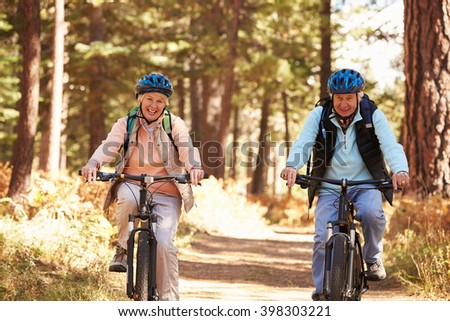 Senior couple cycling on forest trail, California - stock photo