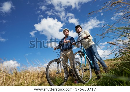 Senior Couple Cycling Through Countryside Together - stock photo