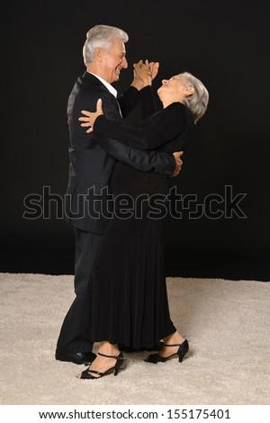 Senior couple dancing on black background - stock photo