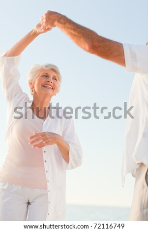 Senior couple dancing on the beach - stock photo