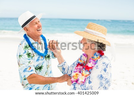 Senior couple dancing together at the beach on a sunny day - stock photo