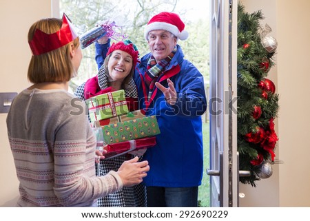 Senior couple delivering presents at Christmas time. They are both smiling and are holding Christmas gifts.  - stock photo