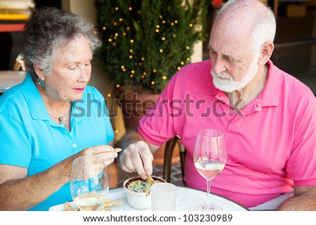 Senior couple dining out, looking serious and not very happy. - stock photo