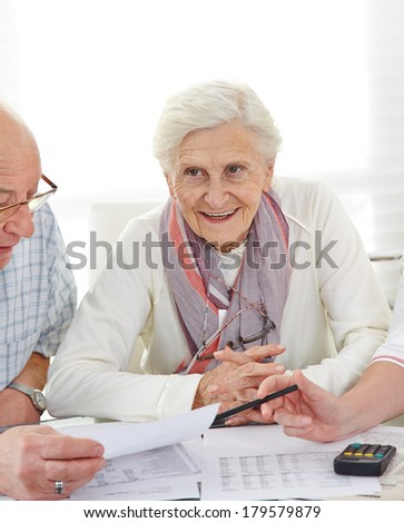 Senior couple discussing their financial situation with bills on the table - stock photo