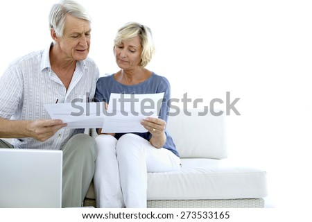 Senior couple doing home finances. White background with copy space. - stock photo