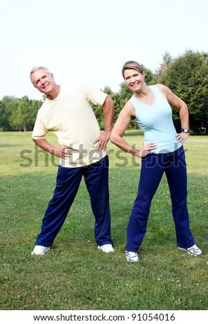 Senior couple doing yoga in the park. - stock photo