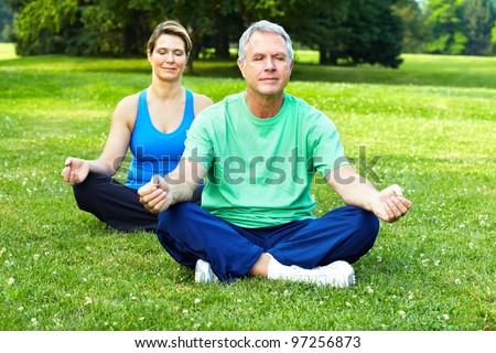 Senior couple doing yoga in the park. Health. - stock photo
