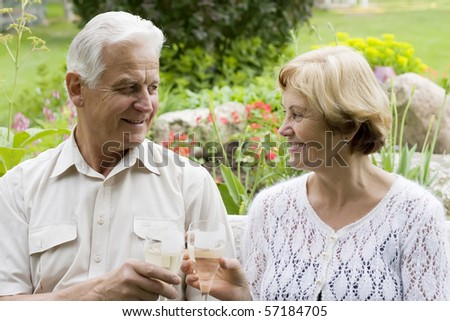 Senior couple drinking champagne in a blossoming garden
