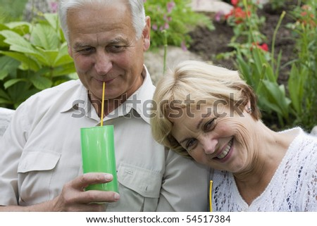 Senior couple drinking cocktails in a blossoming garden