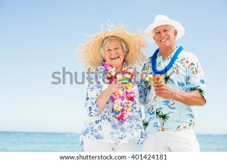 Senior couple drinking cocktails on a sunny day - stock photo