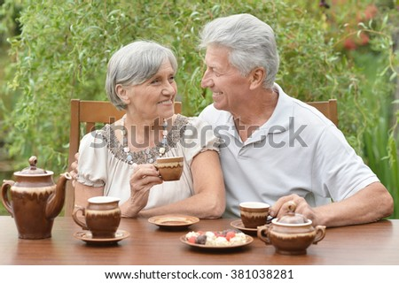 Senior Couple drinking tea in summer garden - stock photo