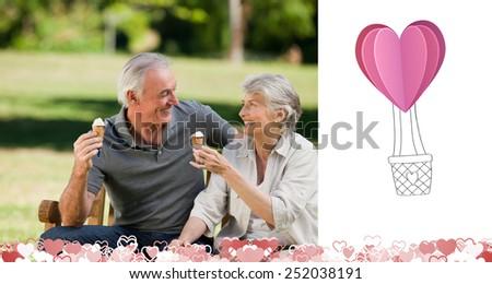 Senior couple eating an ice cream on a bench against heart hot air balloon - stock photo