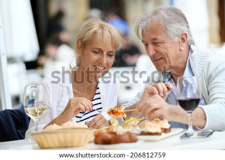 Senior couple eating Spanish fingerfood in Spain - stock photo