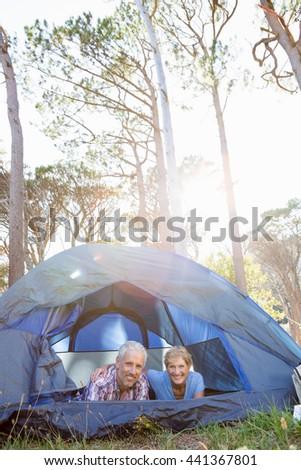 senior couple elongating inside their tent - stock photo