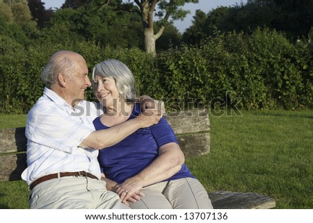 Senior couple embrace whilst seated on a park bench on a summers evening. - stock photo