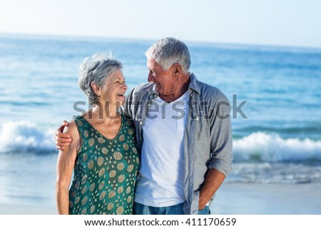 Senior couple embracing at the beach on a sunny day - stock photo