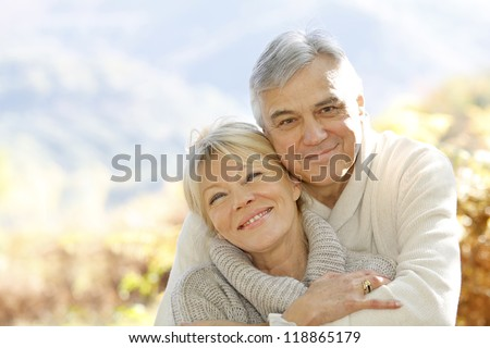 Senior couple embracing each other in countryside - stock photo