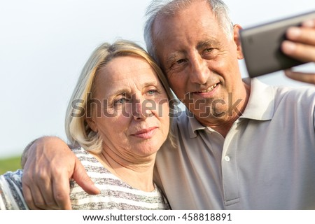 Senior couple embracing each other in countryside and and make selfi with phone. - stock photo
