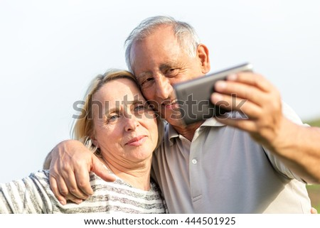 Senior couple embracing each other in countryside and and make selfie with phone - stock photo