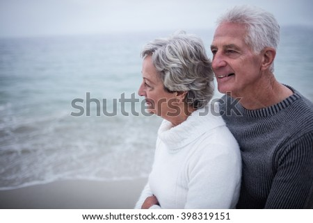 Senior couple embracing each other on the beach on a sunny day - stock photo