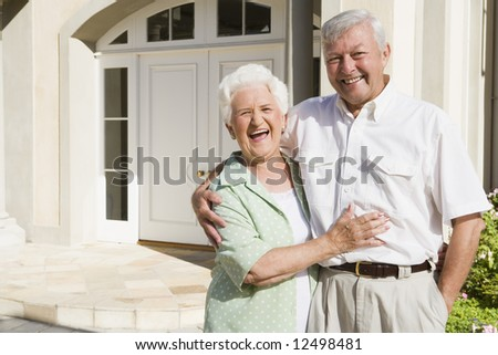 Senior couple embracing outside house - stock photo