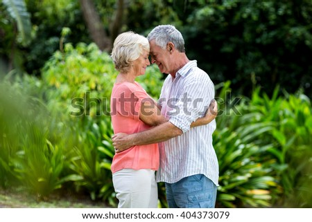 Senior couple embracing while touching head at yard - stock photo
