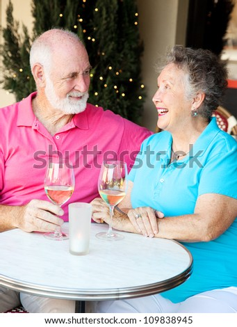 Senior couple enjoying a glass of wine and conversation at an outdoor cafe. - stock photo